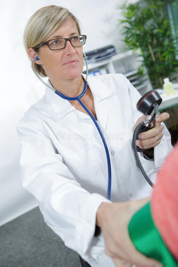Pressione sanguigna di prova di medico al paziente senior fotografia stock libera da diritti