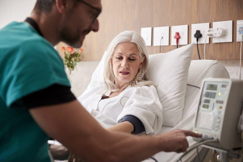 Pressione sanguigna maschio dei pazienti di Taking Mature Female dell'infermiere nel letto di ospedale con la macchina automatizz fotografia stock