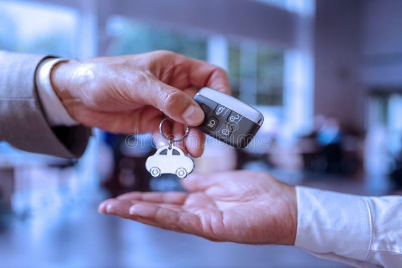presso un concessionario di autoveicoli, un responsabile commerciale consegna un codice di prenotazione a un compratore fotografia stock libera da diritti