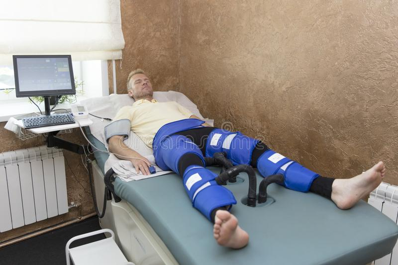 Pressotherapy machine on man in medical spa center. Cosmetic medicine devices stock photos