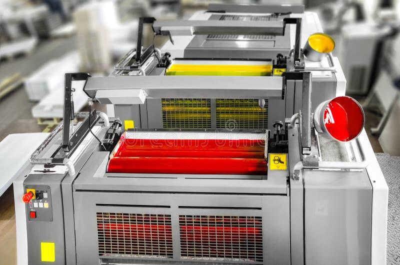 Pressprinting - offset- maskindetalj Magentafärgade och gula enheter arkivfoto