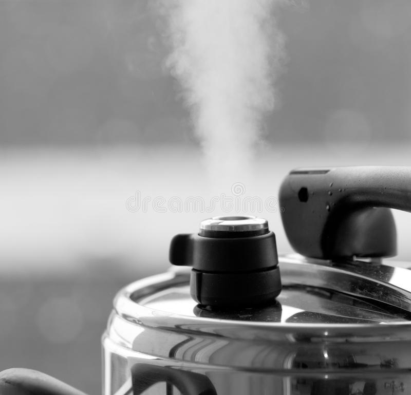 Pressure cooker. Black and white picture of steam escaping from pressure cooker royalty free stock photography