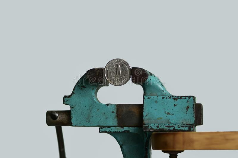 Pressure on the currency. Concept of currency under pressure. US dollar /quarter dollar USD coin being squeezed in jaw vice stock photos