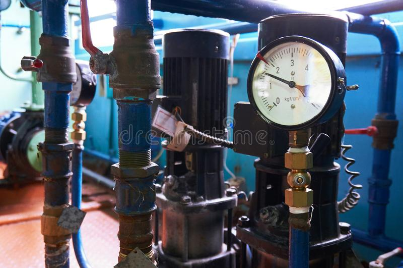 A pressure gauge on the pipeline showing the water pressure after the electric pumps. A pressure gauge on the pipeline showing the water pressure stock photos