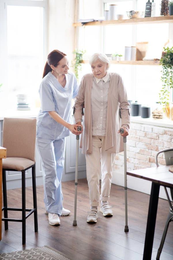 Prestador de cuidados a mulheres que andam de muletas imagens de stock