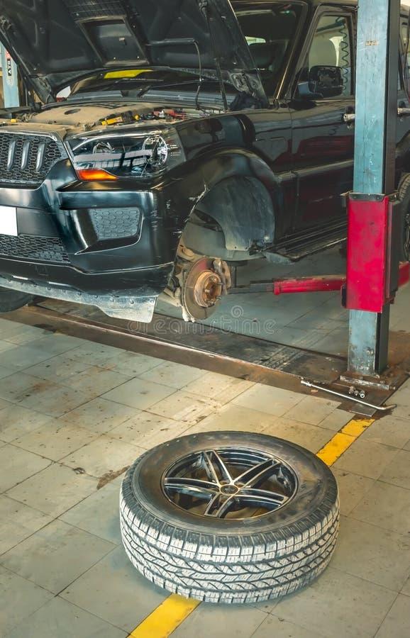 Prestando serviços de manutenção e abrindo ao pneumático do carro foto de stock