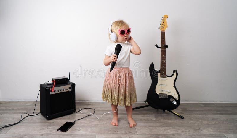Prestazione domestica: Una ragazza si siede sul pavimento che canta con un microfono Vicino sta l'attrezzatura di musica fotografia stock libera da diritti