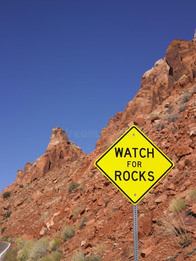 Preste atenção para o sinal das rochas ao lado da estrada imagem de stock