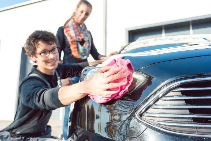 Preste serviços de manutenção à lâmpada da limpeza do homem do veículo na lavagem de carros imagem de stock royalty free