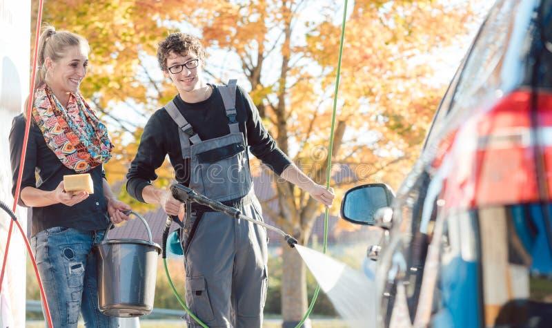 Preste serviços de manutenção à mulher de ajuda do homem que limpa seu automóvel na lavagem de carros imagens de stock royalty free
