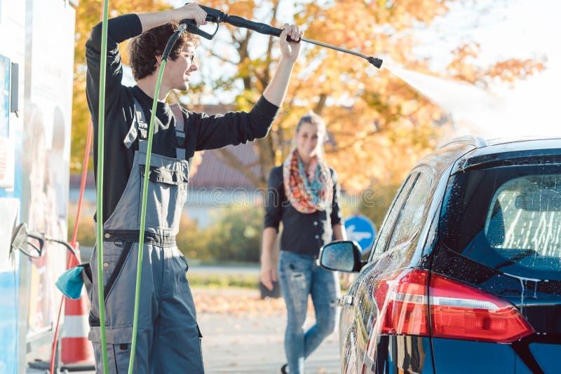 Preste serviços de manutenção à mulher de ajuda do homem que limpa seu automóvel na lavagem de carros imagem de stock royalty free