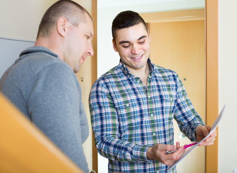 Preste serviços de manutenção ao empregado com o inquilino na entrada fotografia de stock royalty free