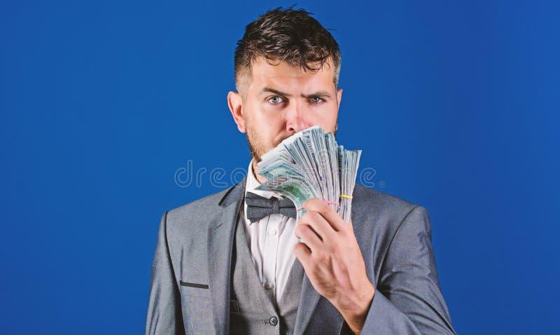 Prestiti di contanti facili Mucchio convenzionale della tenuta del vestito dell'uomo del fondo blu delle banconote del dollaro L' immagini stock libere da diritti