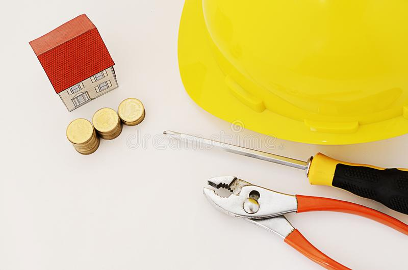 Prestiti immobiliari per la riparazione con il casco e cacciavite e pinze fotografia stock libera da diritti