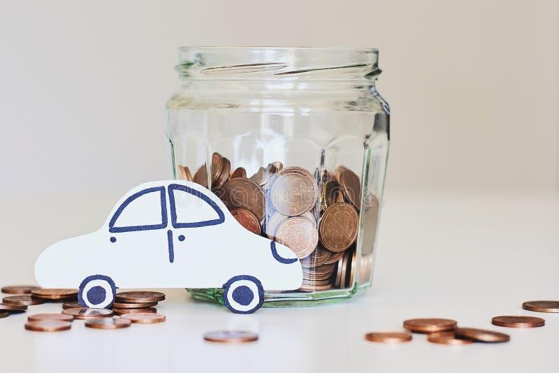 Prestito di automobile, concetto dell'assicurazione auto Barattolo di vetro in pieno delle monete e dell'automobile del Libro Bia fotografie stock libere da diritti