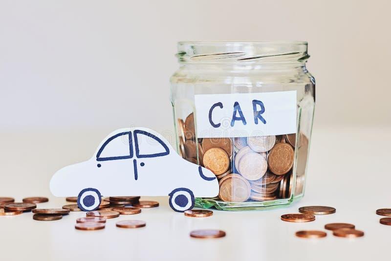 Prestito di automobile, concetto dell'assicurazione auto Barattolo di vetro in pieno delle monete e dell'automobile del Libro Bia fotografia stock