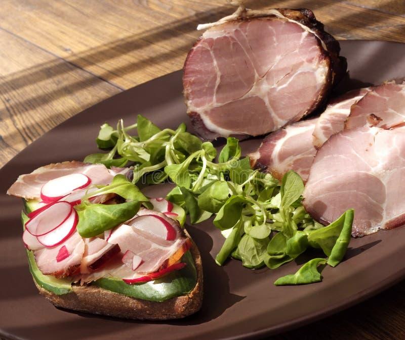 Presunto bruto, secado do presunto defumado com sanduíche e salada na placa na tabela de madeira foto de stock royalty free