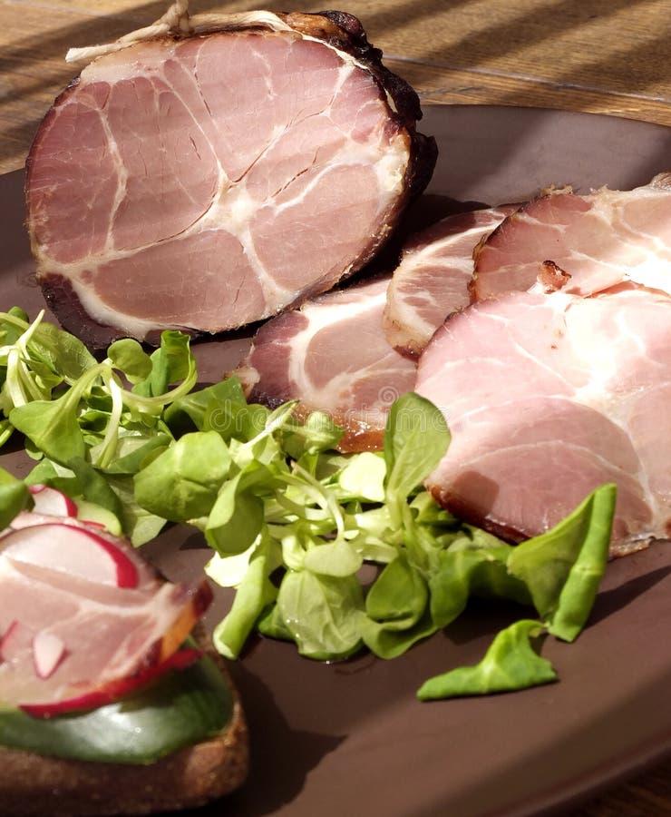 Presunto bruto, secado do presunto defumado com sanduíche e salada na placa na tabela de madeira fotos de stock