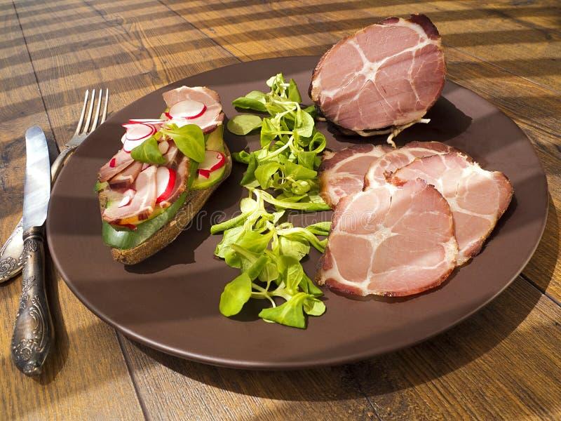 Presunto bruto, secado do presunto defumado com sanduíche, salada na placa imagem de stock