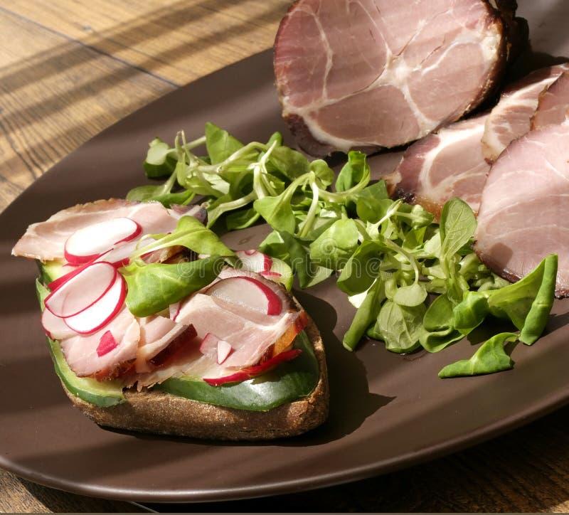 Presunto bruto, secado do presunto defumado com sanduíche, salada na placa imagens de stock