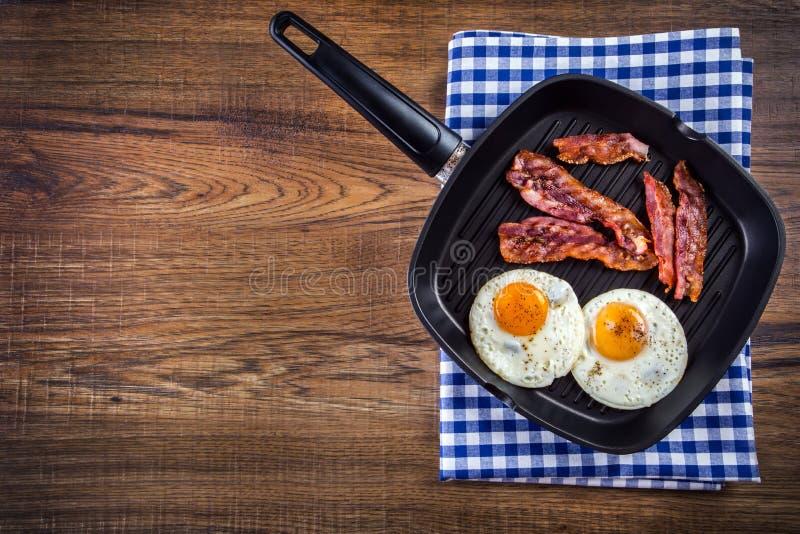 Presunto e ovo Bacon e ovo Ovo salgado e polvilhado com a pimenta preta Bacon grelhado, dois ovos em uma bandeja do Teflon imagens de stock
