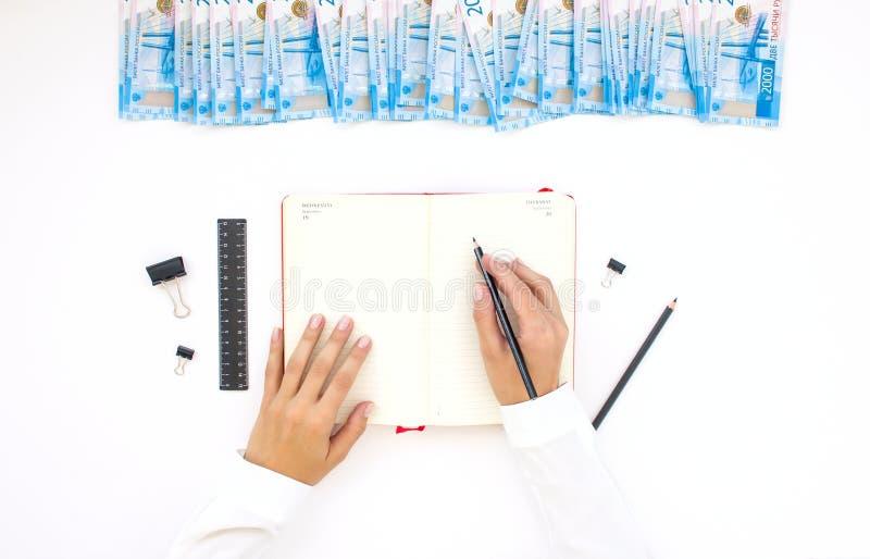 Presupueste el planeamiento, cuaderno, dinero, hucha, visión superior, en la tabla foto de archivo