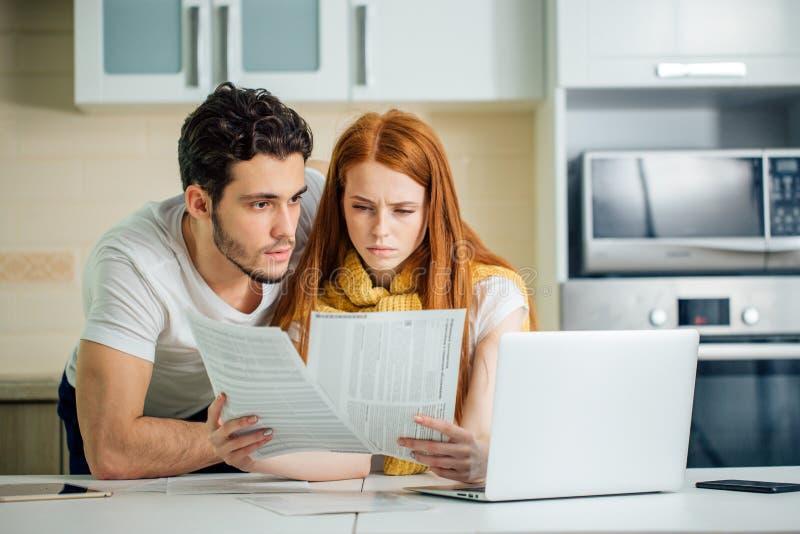 Presupuesto de manejo de la familia, revisando sus cuentas bancarias usando el ordenador portátil en cocina foto de archivo