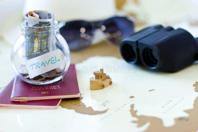 Presupuesto de viaje - ahorros del dinero de las vacaciones en un tarro de cristal en el mundo m fotos de archivo libres de regalías
