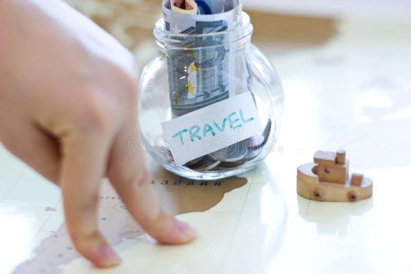 Presupuesto de viaje - ahorros del dinero de las vacaciones en un tarro de cristal en el mundo m imagen de archivo