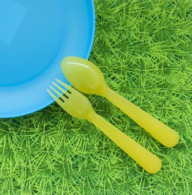 Pret gekleurde achtergrond met lepels, vorken, schotel op groen gras stock afbeeldingen