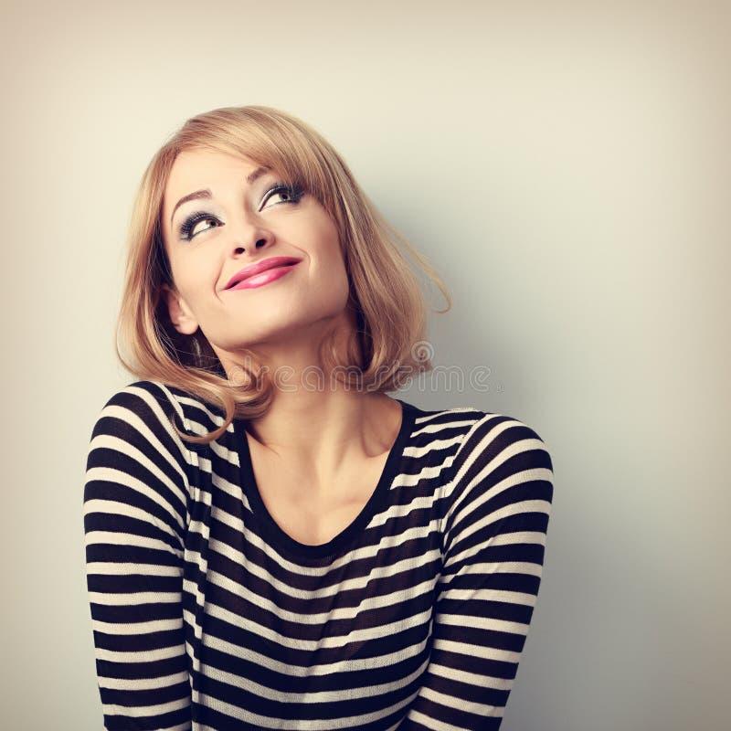 Pret mooie denkende blonde jonge vrouw die in sweater omhoog kijken stock foto's