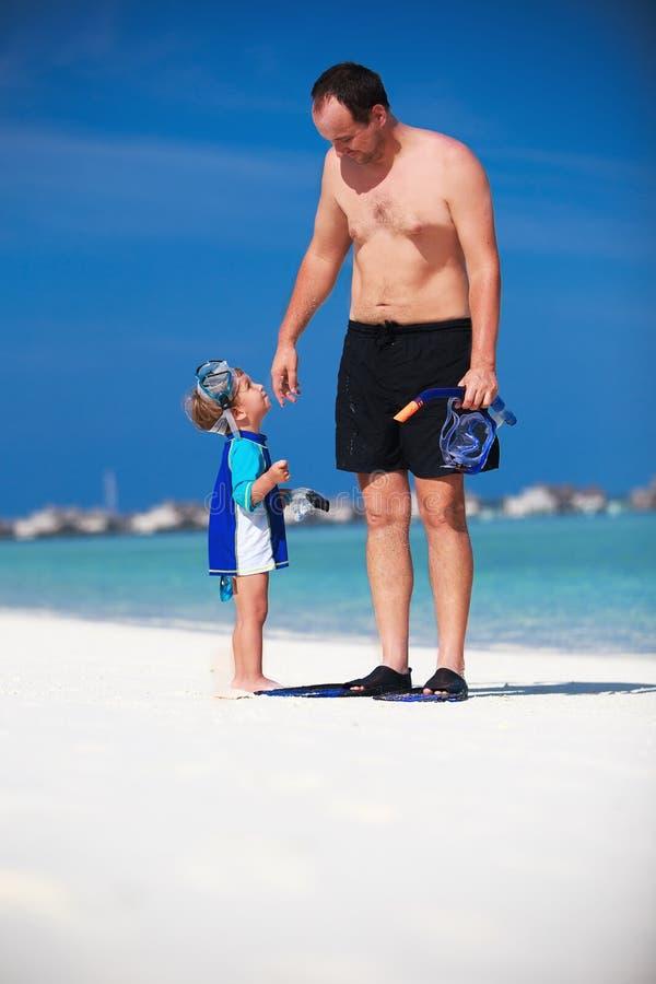 Pret op het strand hebben en vader en zijn zoon die klaar aan snorkle worden royalty-vrije stock afbeelding