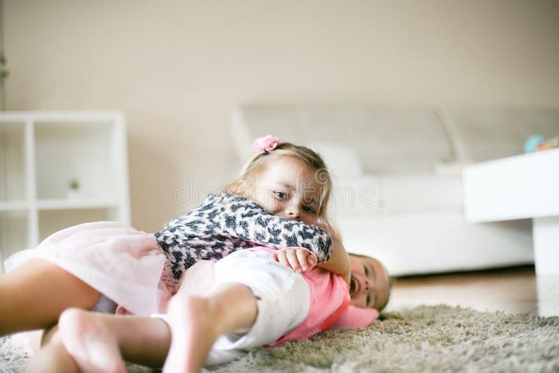 Pret op vloer Meisjes die thuis spelen stock afbeelding