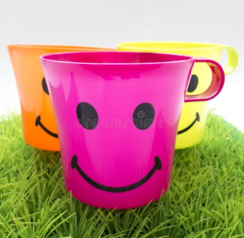 Pret plastic koppen met een glimlach op het groene gazon stock afbeelding