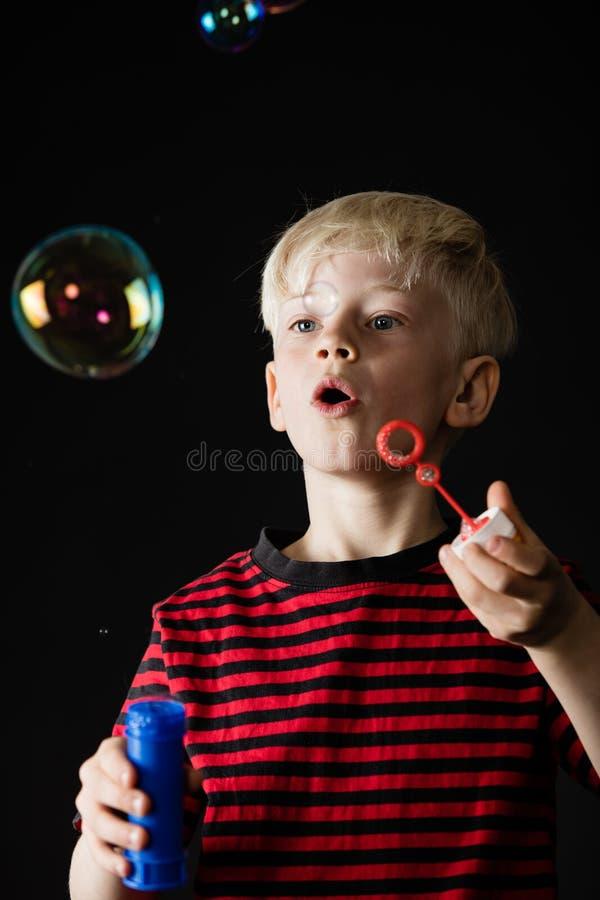 Pret weinig jongens blazende zeepbels stock afbeelding