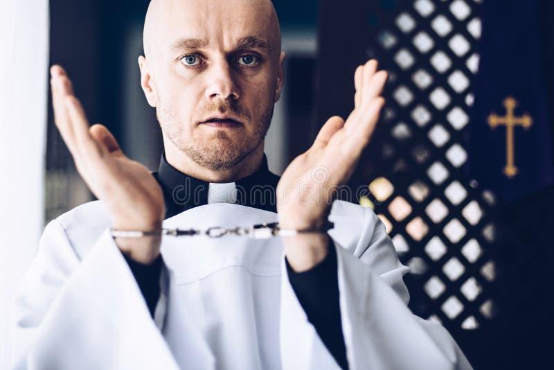 Prete cattolico in manette in chiesa fotografia stock