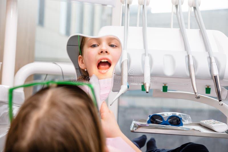 Preteen девушка смотря ее зубы в зеркале в педиатрической зубоврачебной клинике стоковое фото