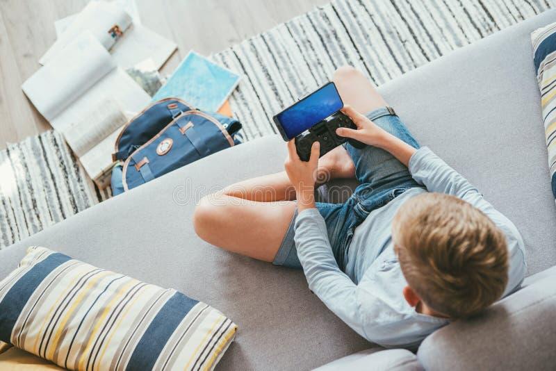 Preteen мальчик забыл об его уроках и книгах и играет wi игр стоковая фотография rf