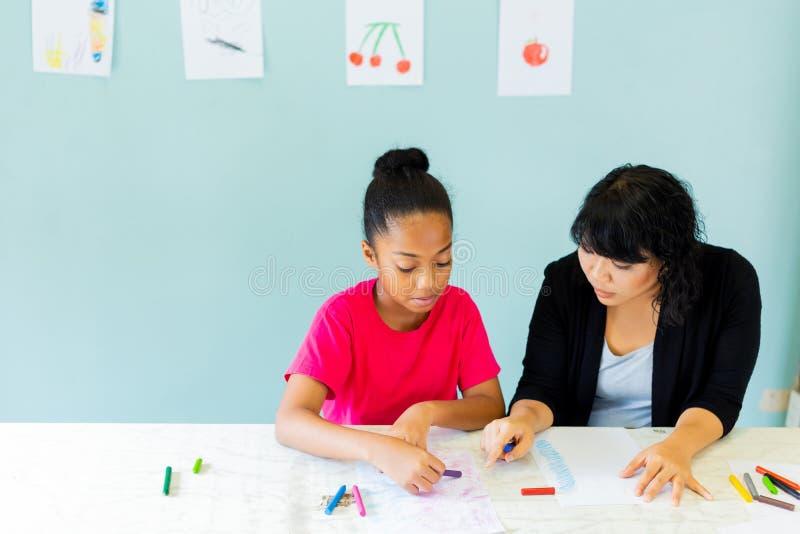 Preteen afrikansk amerikanunge tillsammans med med asiatiska lärareundervisningkonster royaltyfria bilder
