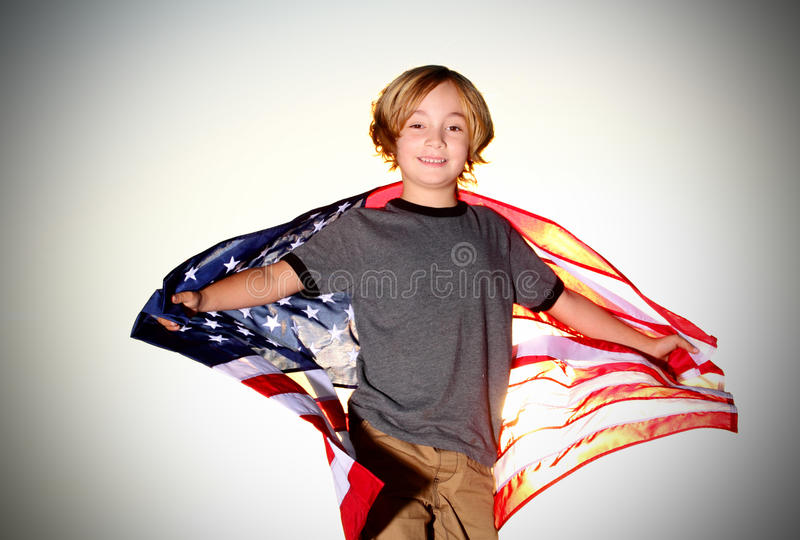 Preteen Boy with American Flag. Blond little patrioctic 7 year old boy with an American flag. Shallow depth of field royalty free stock images