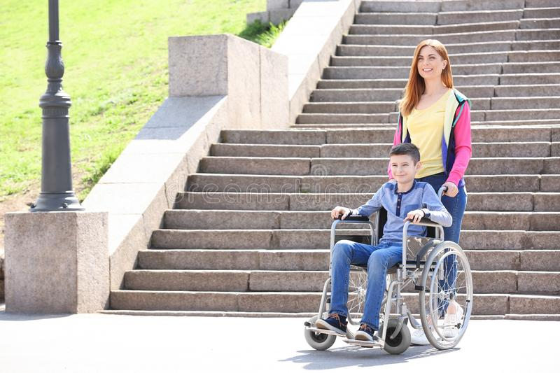 Preteen boy in wheelchair with his mother royalty free stock photography