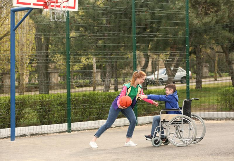 Preteen boy in wheelchair and young woman playing basketball royalty free stock photo