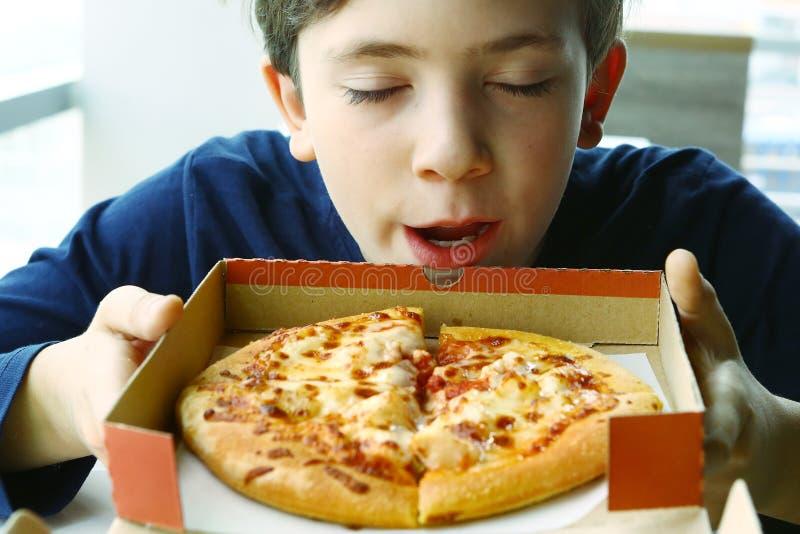 Preteen chłopiec odoru przystojna pizza w pudełku obraz stock