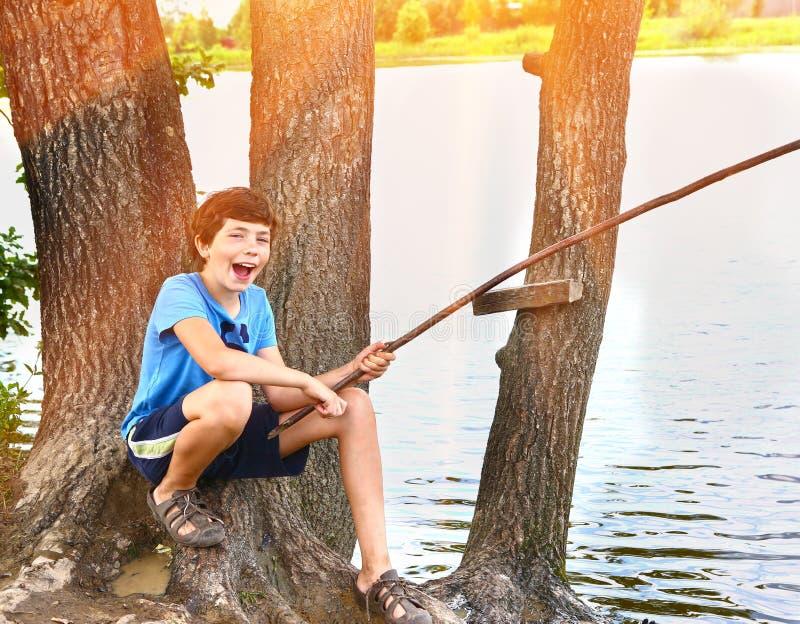 Preteen chłopiec szczęśliwy połów na jeziornym zakończeniu up obrazy stock