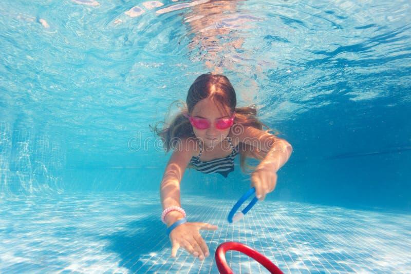 Preteen dziewczyna trenuje pod wodą w różowych gogle obraz royalty free