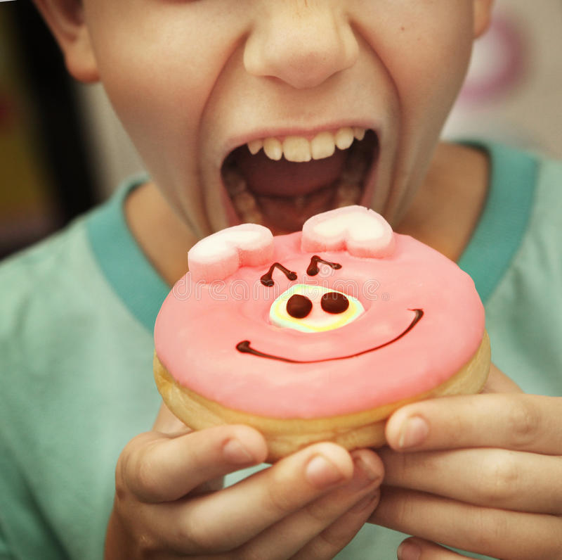 Preteen by eat doughnut with pig glaze close up stock photo