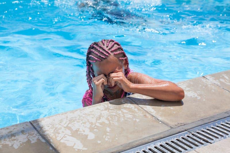 Preteen flicka som torkar vatten från ögon, när simma i pöl arkivfoto