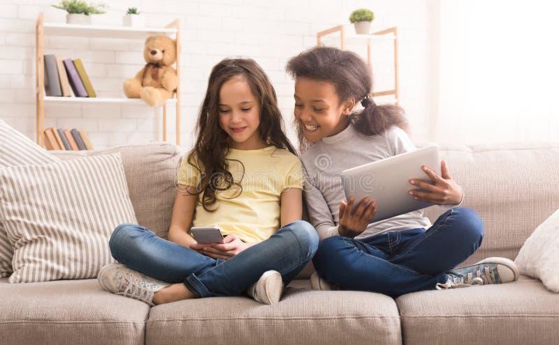 Preteen flickor med grejer som hemma sitter på soffan royaltyfria foton