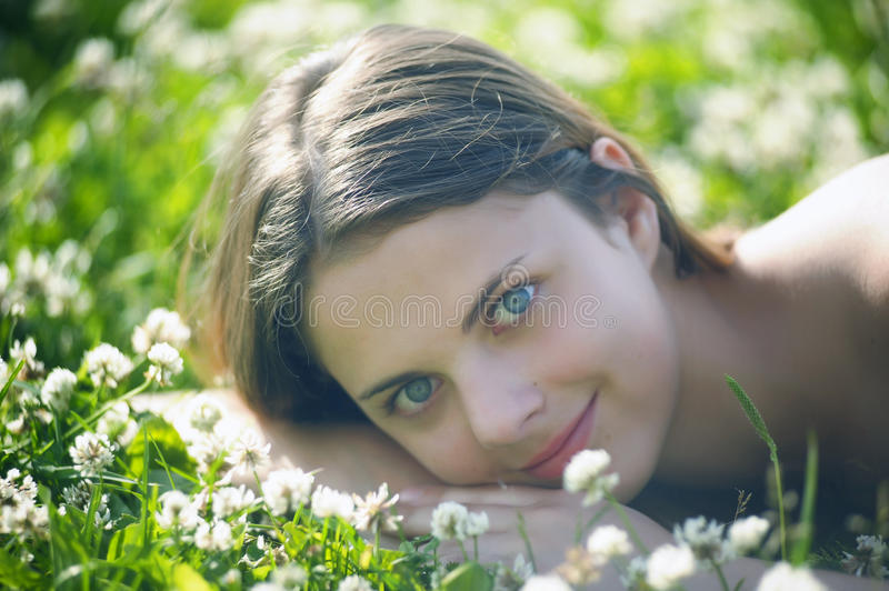 Little Smiling Girl Sitting In The Field Of Grass Stock