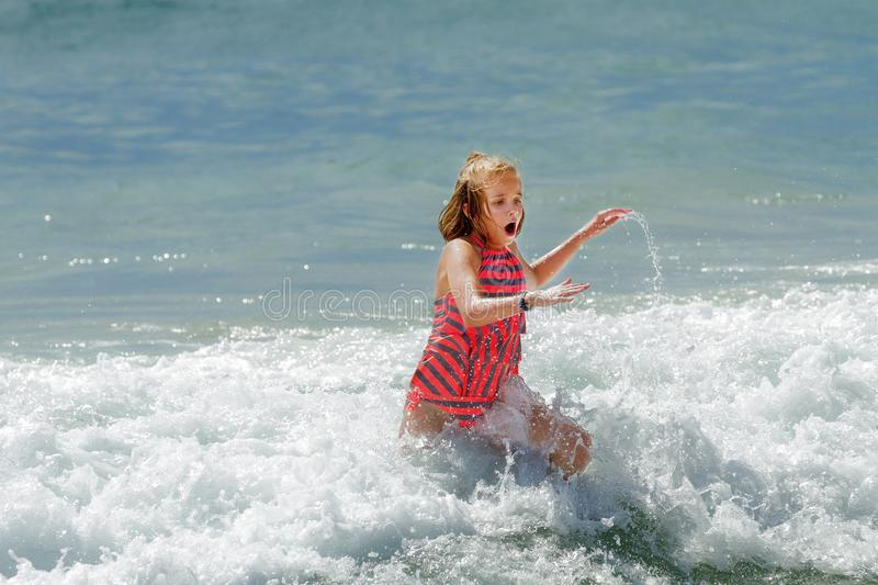 PreTeen Girl Running Out of the Cold Ocean Water Her Mouth is Op. Pre-teen girl runs out of Pacific ocean waves. Her mouth is open because of the chill and she royalty free stock photo